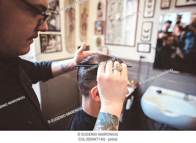 Barber combing gel into clients hair in barber shop