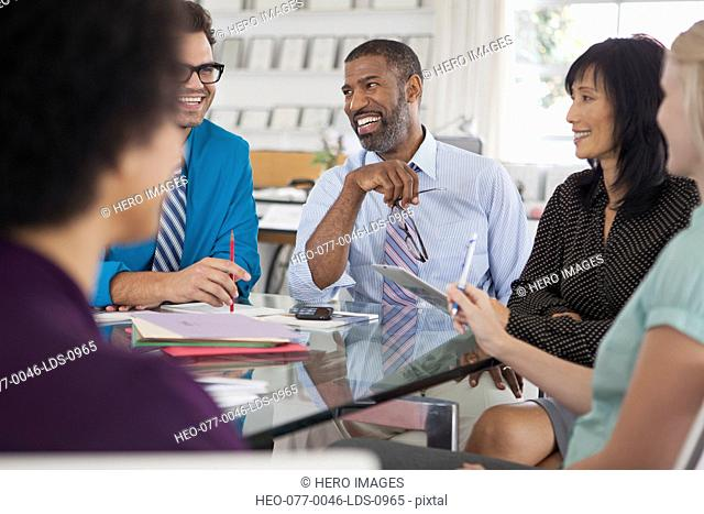five businesspeople having a laugh while meeting