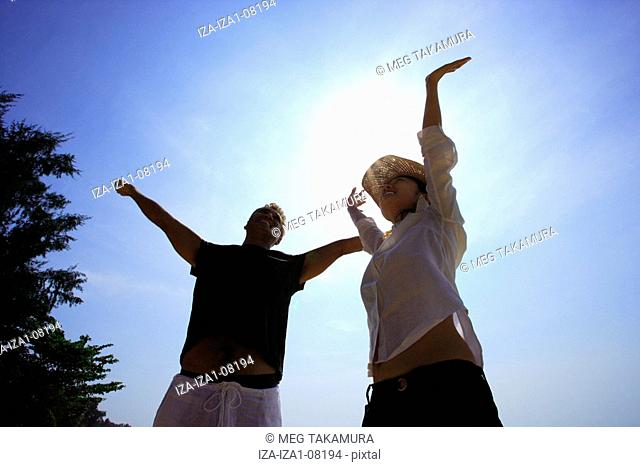Low angle view of a mid adult man and a young woman standing on the beach with their arms raised