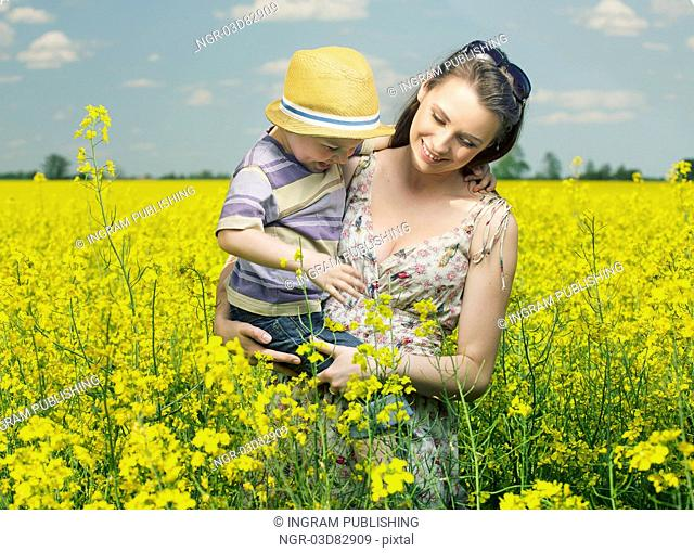 Mother and son walking among the canola flowers