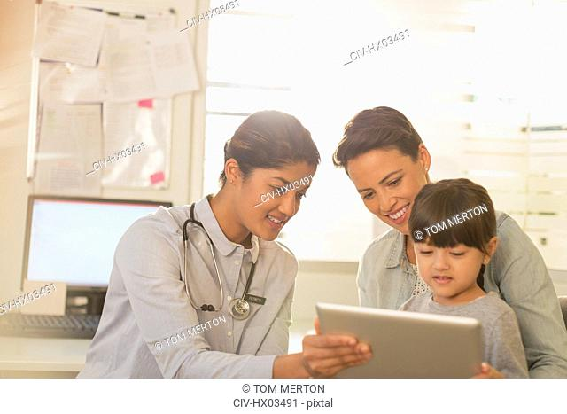 Female pediatrician showing digital tablet to girl patient and mother in examination room