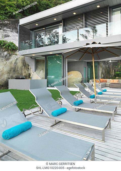 Row of lounge chairs outside modern home