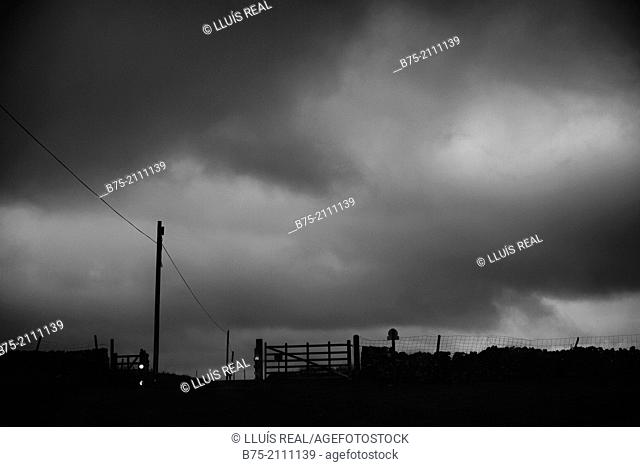 Rural landscape with electric poles and barriers with stormy sky at sunset in Yorkshire Dales, England, UK, Europe
