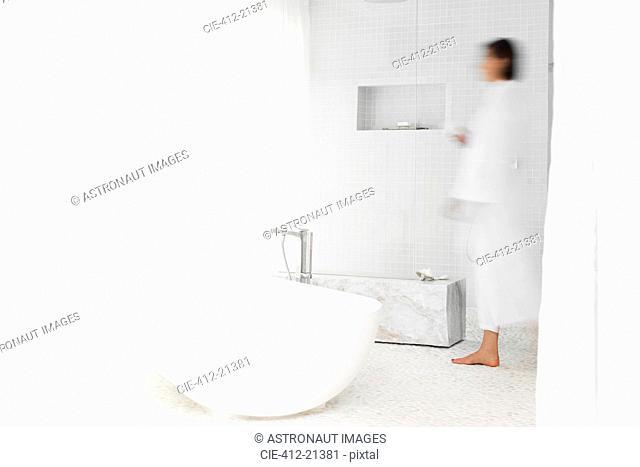 Blurred view of woman walking in modern bathroom