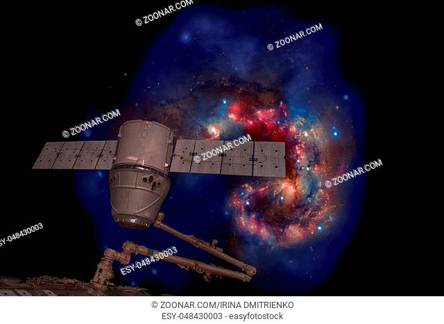 SpaceX Dragon over spiral galaxy. Elements of this image furnished by NASA