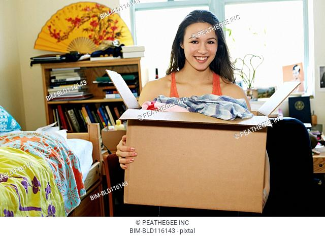 Mixed race college student unpacking in dorm