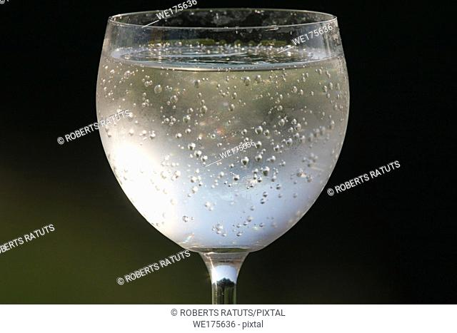 Fragment of glass filled with sparkling drink in the nature.