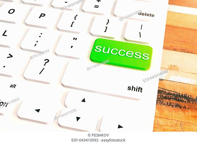 Closeup of white keyboard with green success button on wooden desktop. 3D Rendering