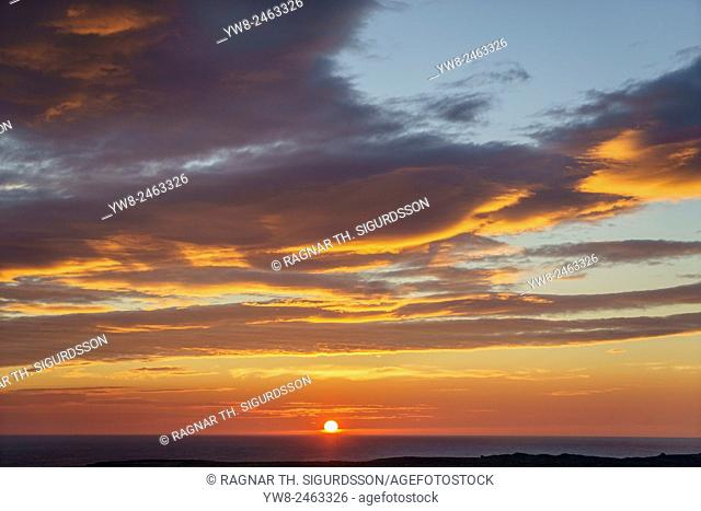 Sunset over the ocean by Londrangar sea stacks and the Thufubjarg cliffs, Snaefellnes Peninsula, Iceland