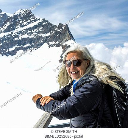 Portrait of smiling Caucasian woman leaning on railing near mountains