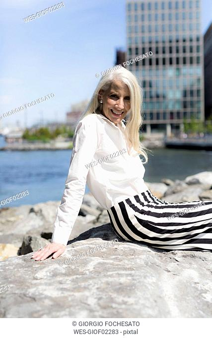 USA, Brooklyn, portrait of smiling mature woman sitting on a wall