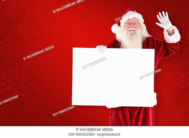 Composite image of santa holds a sign and is waving