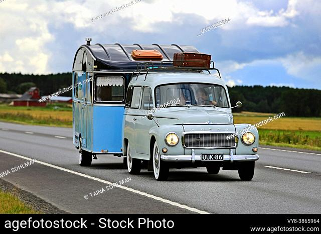 Classic Volvo car PV544, manufactured 1958-65 by Volvo, pulls blue vintage caravan along highway in the summer. Jalasjarvi, Finland. 2016