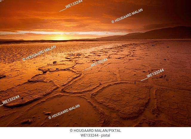 Landscape photo of a flaiming red sunset over the plains of the Tsauchab dune valley in the heavy rains of 2011. Sossusvlei, Namib Naukluft National Park