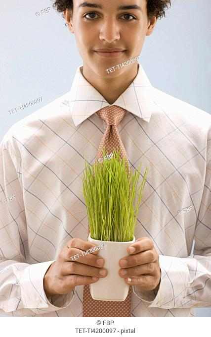 Studio portrait of young man holding wheat grass
