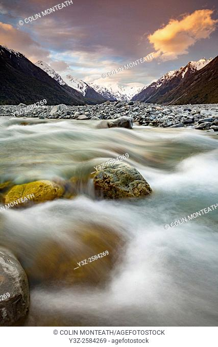 Mathias River at dusk, snow-covered peaks of Southern Alps beyond, Canterbury, New Zealand