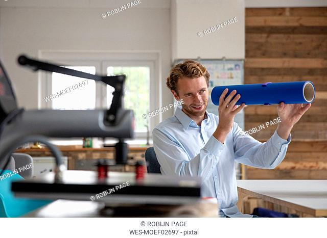 Young businessman in his office, looking through blue pipe