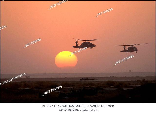 IRAQ -- 02 Apr 2003 -- Army HH-60 Blackhawk helicopters fly past the setting sun at an air base in southern Iraq. USAF photo -- Picture by Shane A Cuomo / USAF...
