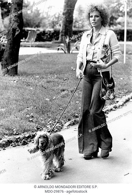 Ornella Vanoni walking with a dog. The Italian actress and singer Ornella Vanoni strolling with her cocker Spaniel dog in Versilia