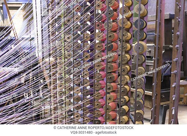 Dynamically lit skeins of brightly coloured thread on metal racks of wooden spools in traditional jacquard textile weaving, La Manufacture de Roubaix, France