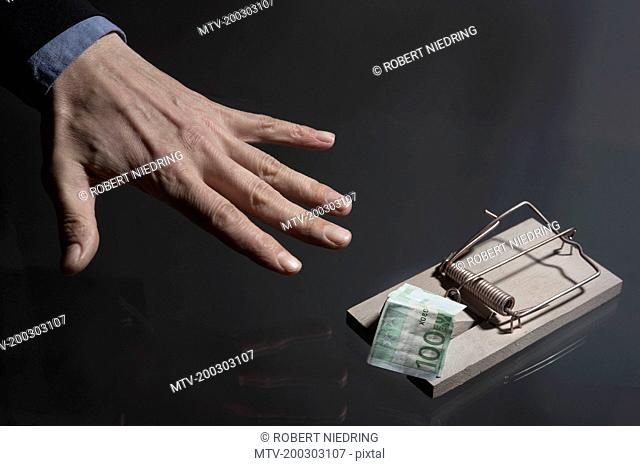 Businessman's hand reaching for money in mousetrap, Bavaria, Germany