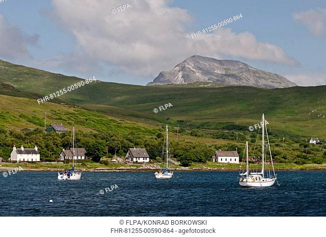 View of yachts moored in bay, with Beinn an Oir, Paps of Jura in background, Craighouse Bay, Isle of Jura, Inner Hebrides, Scotland