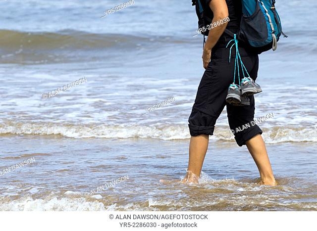 Female backpacker walking in the sea at Saltburn by the sea, north east England. UK