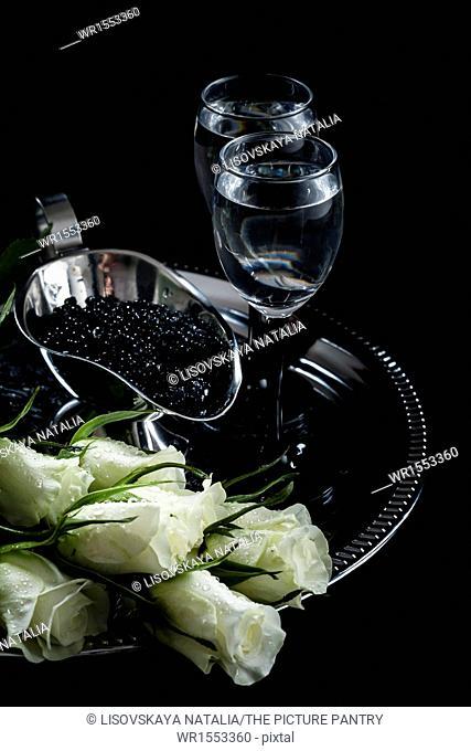 Vodka and black caviar on black background