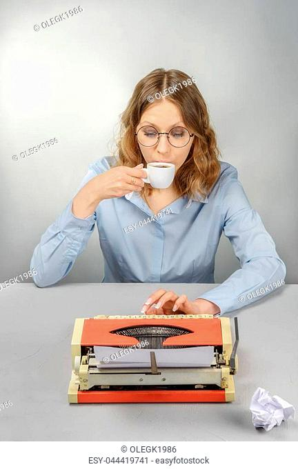 The secretary, wearing glasses behind a typewriter, drinks coffee on a gray background