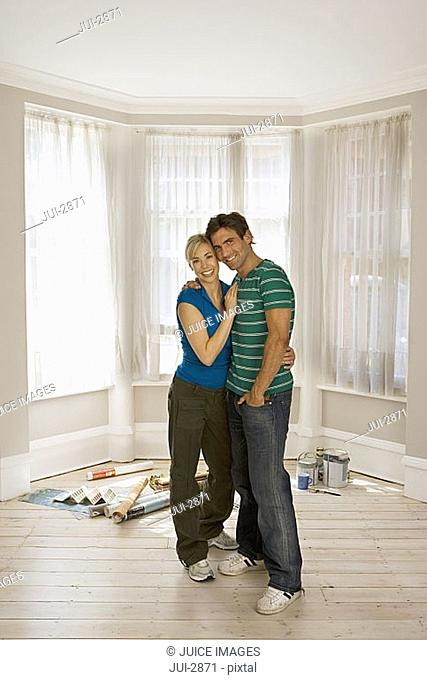 Couple decorating at home, standing in sparse room, smiling, portrait, wallpaper and paint on floor