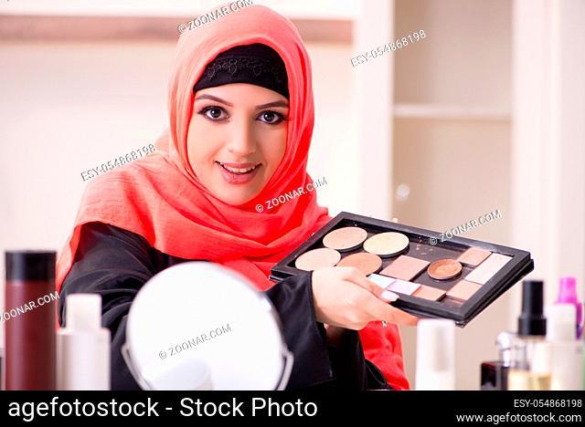 Beautiful woman in hijab applying make-up
