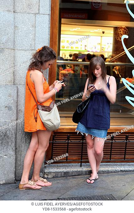 Young tourists checking their messages on their phones cellulare in the Puerta del Sol, Madrid, Spain, Europe