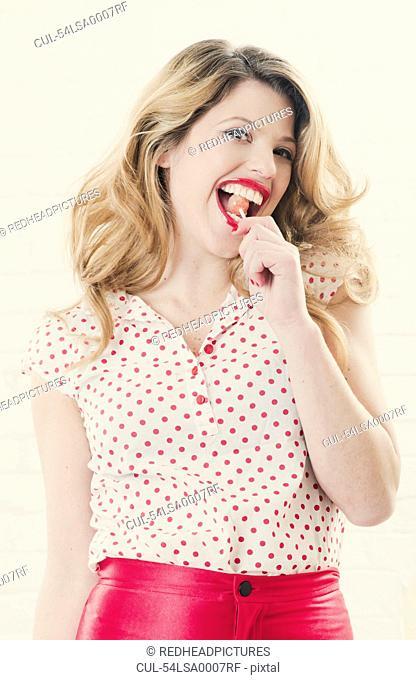 Smiling woman eating lollipop