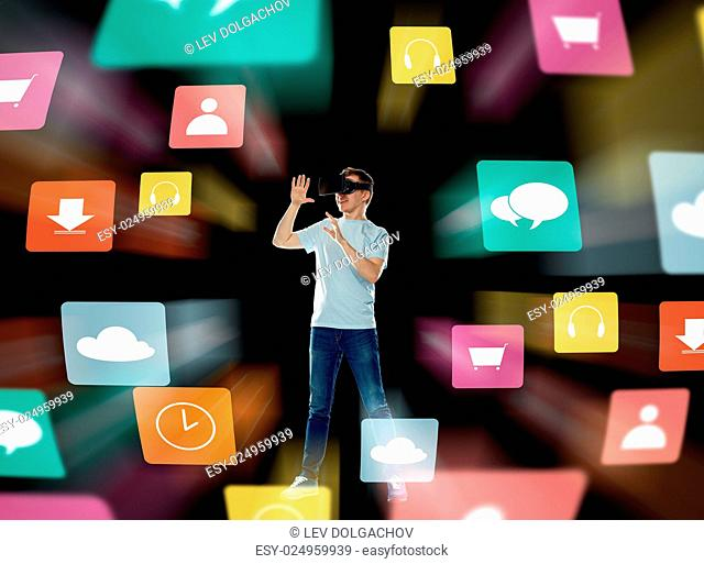 3d technology, augmented reality, gaming, cyberspace and people concept - happy young man in virtual reality headset or 3d glasses with menu icons over black...