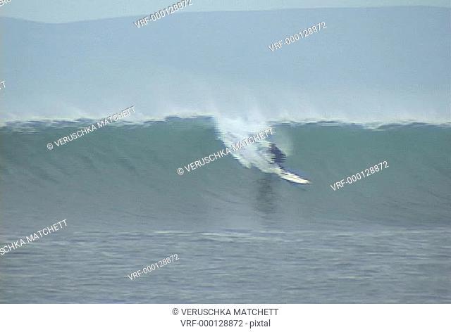 Wide shot Surfer, right hander doing cut backs on big waves. Scotland, UK