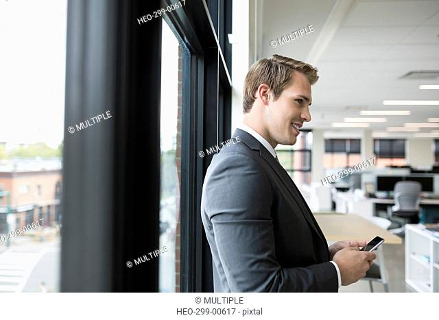 Smiling businessman texting with cell phone at office window