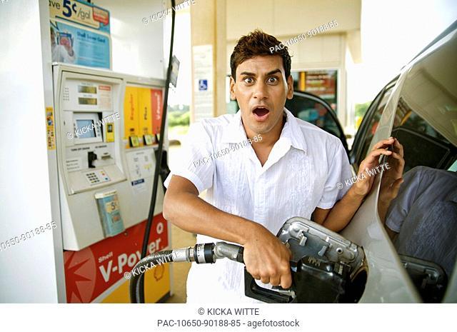 Hawaii, Kauai, Kilauea, Young man putting gas in his vehicle