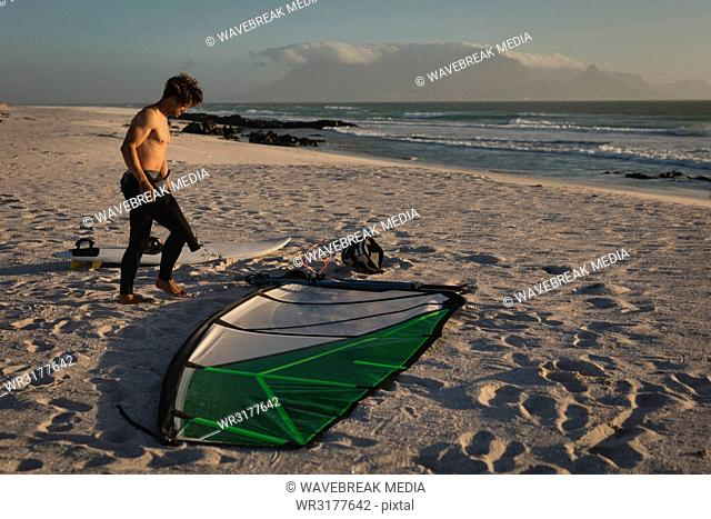 Male surfer standing with kite and surfboard on the beach