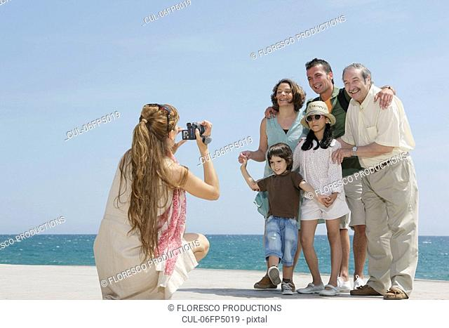 Mother taking video of family by sea