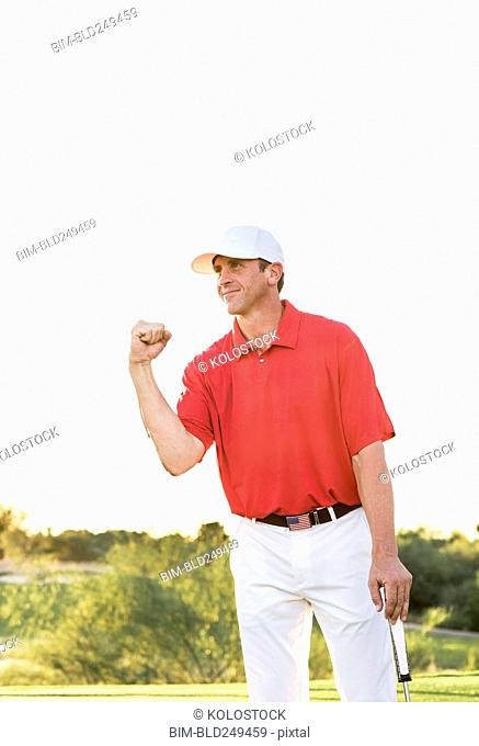 Hispanic golfer celebrating on golf course