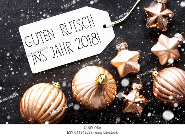Label With German Text Guten Rutsch Ins Jahr 2018 Means Happy New Year 2018. Bronze Christmas Tree Balls On Black Paper Background With Snowflakes