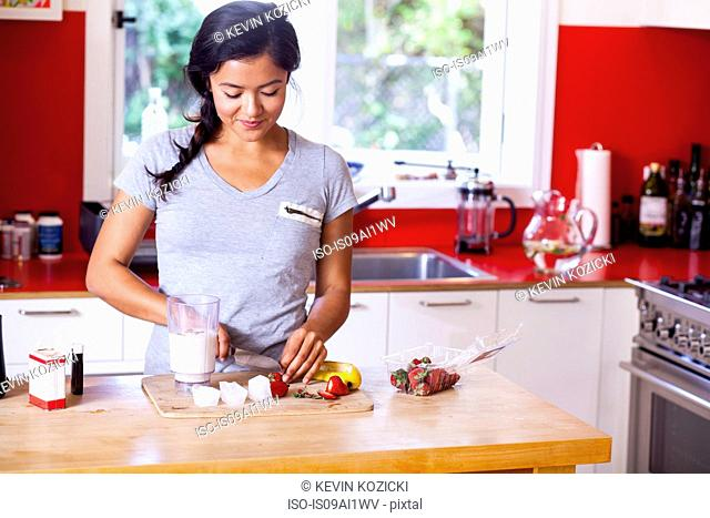 Young woman slicing strawberry in kitchen