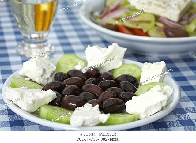 Plate with olives feta and cucumber on table Greek salad and retsina in background