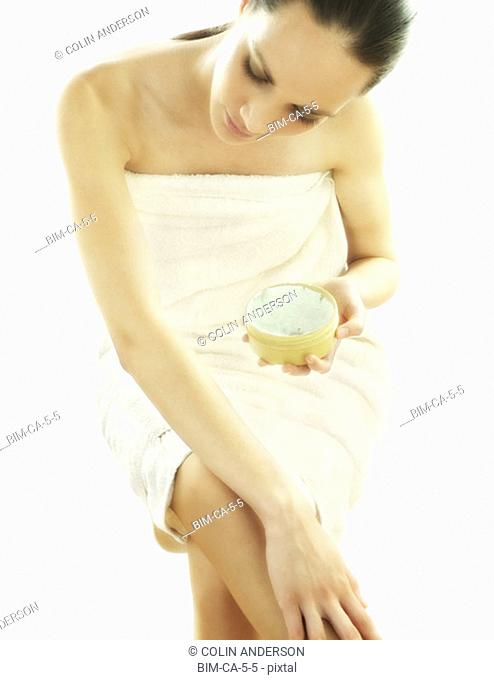 Young woman applying skin lotion