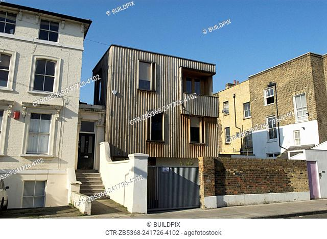 Individually designed timber-cladded house built on a plot surrounded by Victorian housing, East London, UK