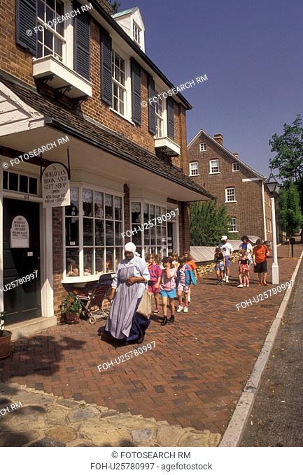 Old Salem, Moravian, Winston-Salem, North Carolina, A group of children follow an interpreter along the cobblestone sidewalk in Old Salem