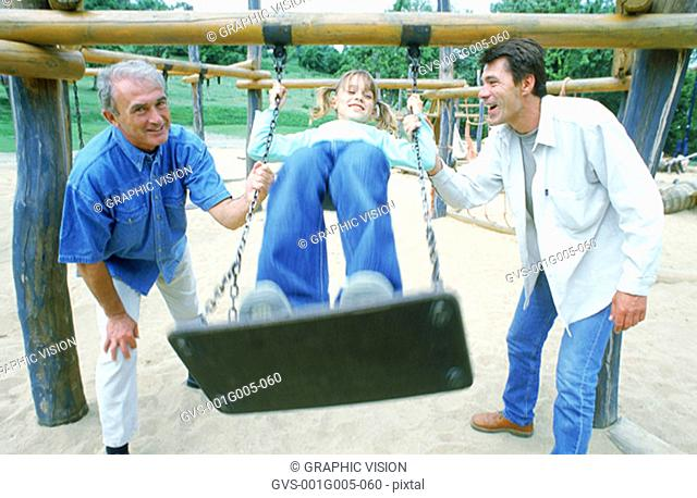 Two men pushing young child on a swing