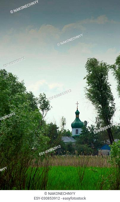 Village Church on a background of green meadows