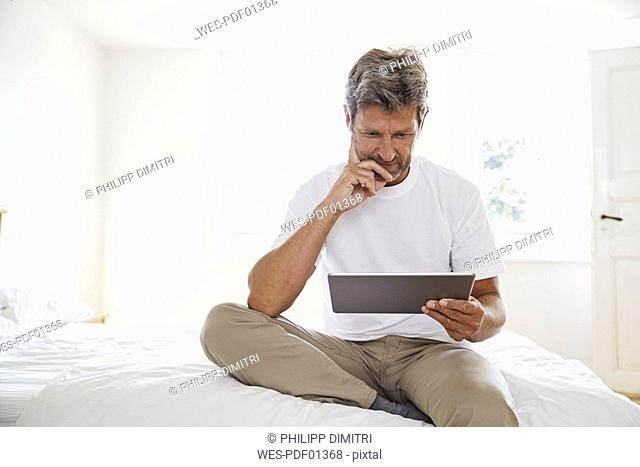 Portrait of mature man with digital tablet in bedroom