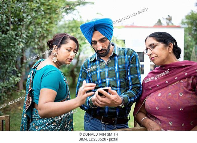 Family texting on cell phone outdoors